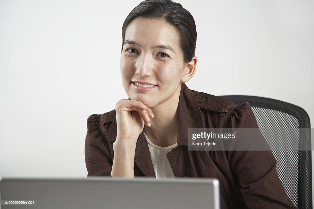Portrait of woman sitting behind laptop : Stockfoto