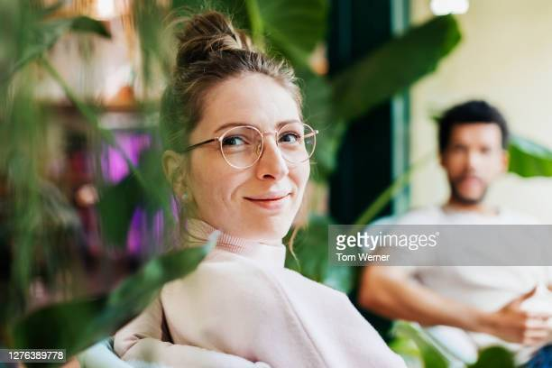 portrait of woman sitting between plants in café - confidence stock pictures, royalty-free photos & images