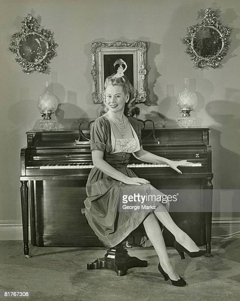 Portrait of woman sitting by piano at home