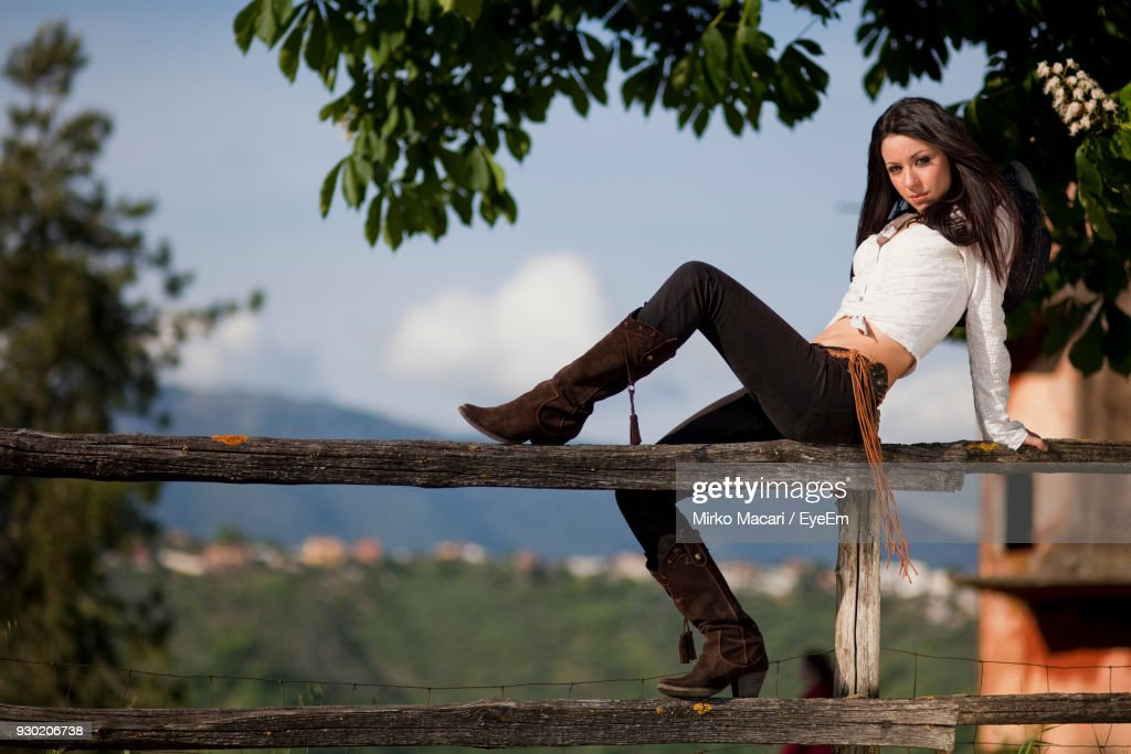 https://media.gettyimages.com/photos/portrait-of-woman-sitting-fence-picture-id930206738