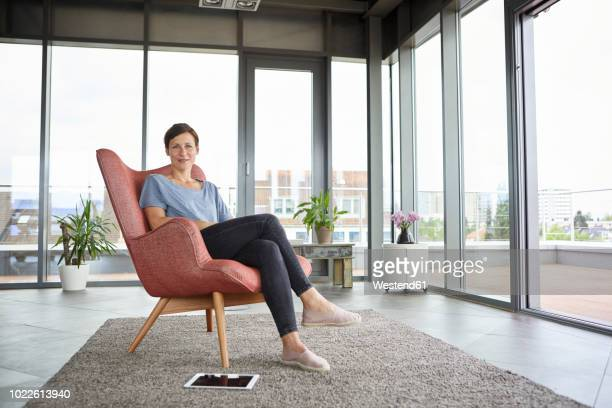 portrait of woman sitting in armchair at home with tablet beside her - chair stock pictures, royalty-free photos & images