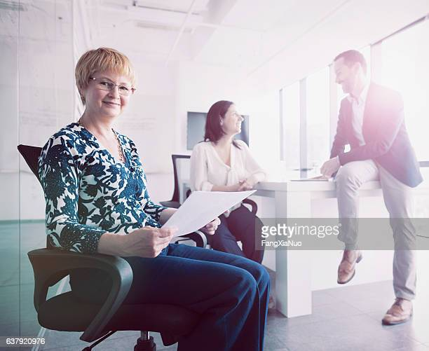 Portrait of woman sitting in chair during meeting