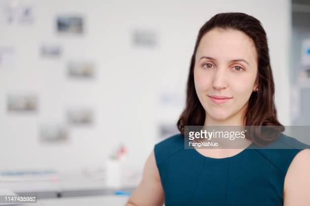 portrait of woman sitting in design office - museum curator stock pictures, royalty-free photos & images