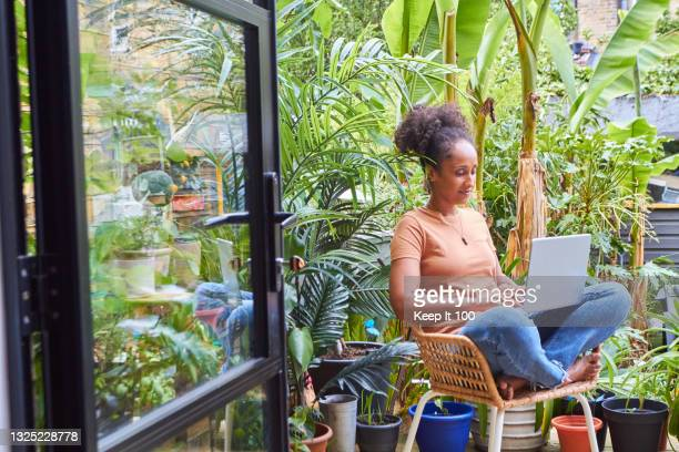 portrait of woman sitting in her garden using a laptop - one mid adult woman only stock pictures, royalty-free photos & images