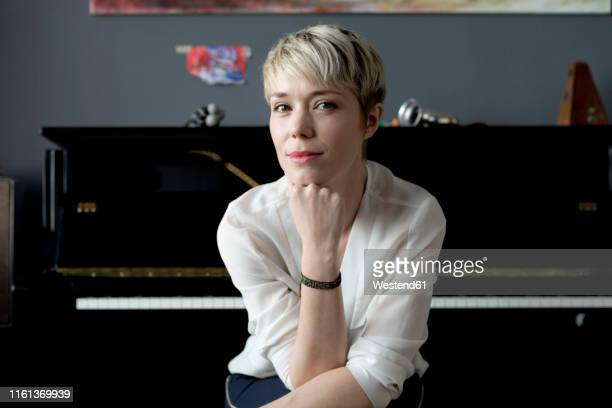 portrait of woman sitting in her music room in front of piano - kurzes haar stock-fotos und bilder