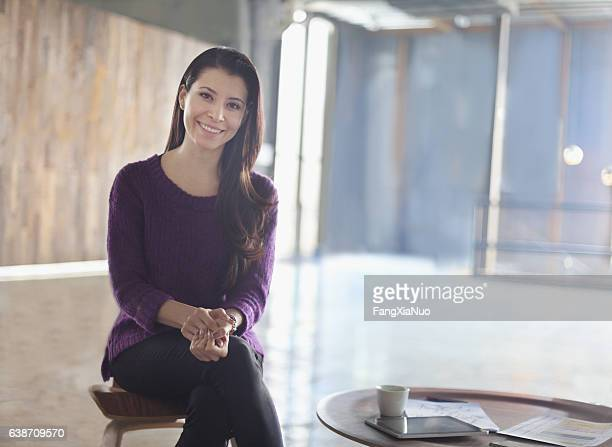 Portrait of woman sitting in large open office studio environment