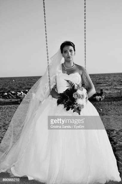 Portrait Of Woman Sitting In Swing At Beach Against Sky