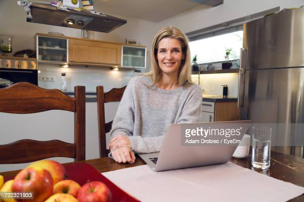 Portrait Of Woman Sitting In The Kitchen