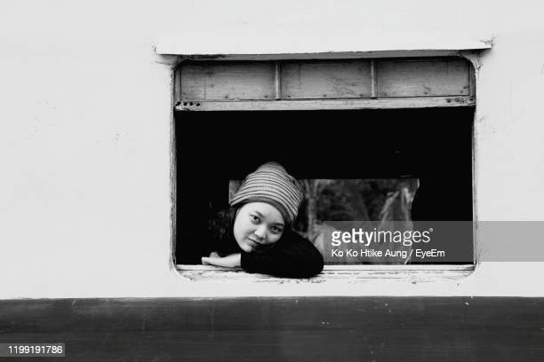 portrait of woman sitting in window - ko ko htike aung stock pictures, royalty-free photos & images