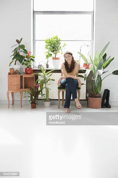Porträt der Frau sitzt in der Nähe von vielen Pflanzen im Hause