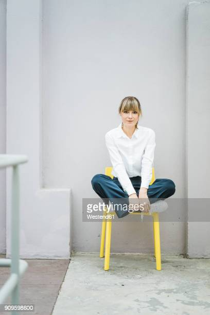 portrait of woman sitting on a chair - sitzen stock-fotos und bilder