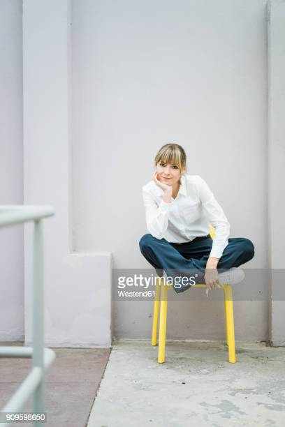 portrait of woman sitting on a chair - ganzkörperansicht stock-fotos und bilder