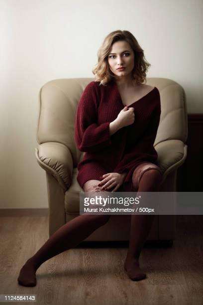 portrait of woman sitting on armchair - mulher fatal imagens e fotografias de stock