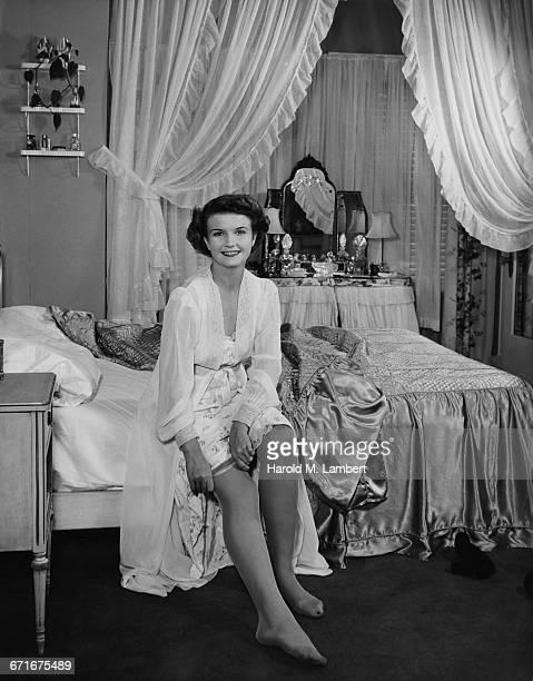 portrait of woman sitting on bed and smiling  - {{ contactusnotification.cta }} stockfoto's en -beelden