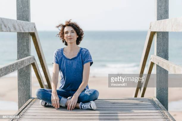 portrait of woman sitting on boardwalk at the beach - une seule femme d'âge moyen photos et images de collection
