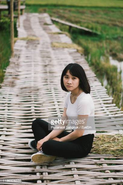 portrait of woman sitting on boardwalk - pattanasit stock pictures, royalty-free photos & images
