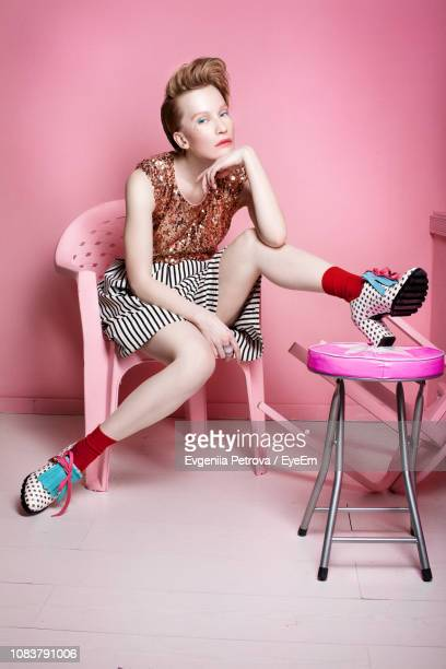 portrait of woman sitting on chair against pink wall - pink dress stock pictures, royalty-free photos & images