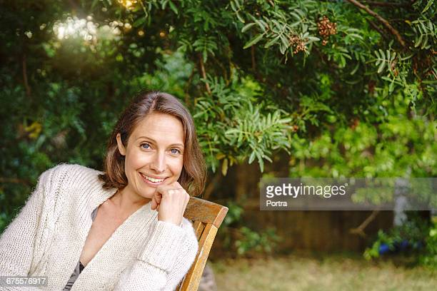 Portrait of woman sitting on chair  against tree