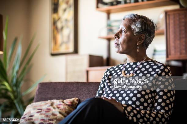 portrait of woman (60yrs) sitting on couch at home - solitario foto e immagini stock