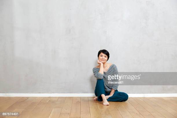 portrait of woman sitting on floor - barefoot woman stock pictures, royalty-free photos & images