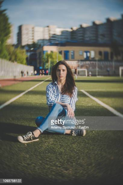 portrait of woman sitting on grass - 18 19 years stock pictures, royalty-free photos & images