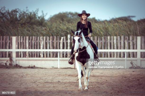 portrait of woman sitting on horse in ranch against sky - 手綱 ストックフォトと画像