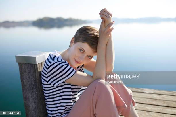 Portrait of woman sitting on jetty at lake