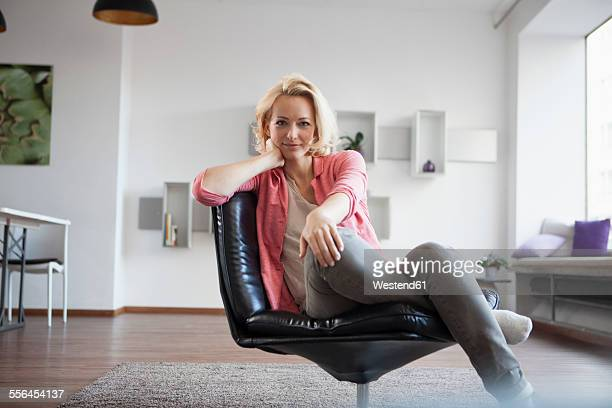 Portrait of woman sitting on leather chair at home