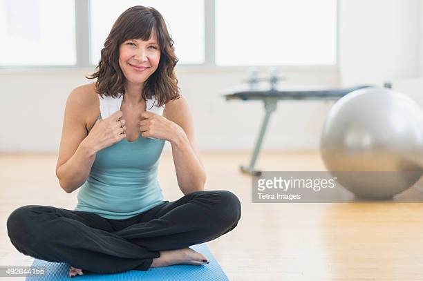 portrait of woman sitting on mat in gym, jersey city, new jersey, usa - sportswear stock pictures, royalty-free photos & images