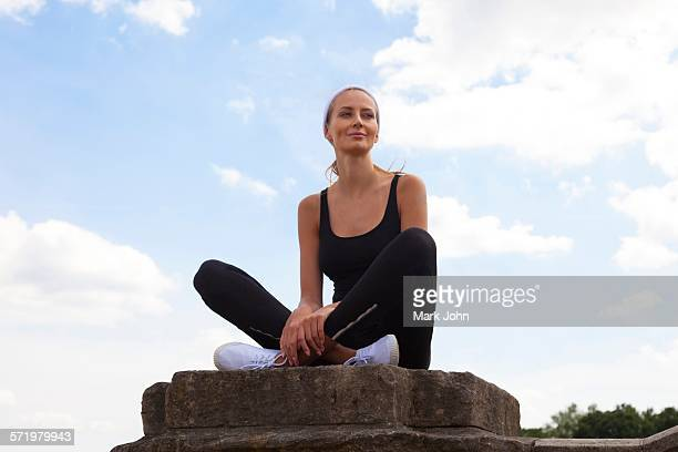 Portrait of woman sitting on pedestal