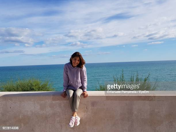 portrait of woman sitting on retaining wall against sea - retaining wall stock pictures, royalty-free photos & images