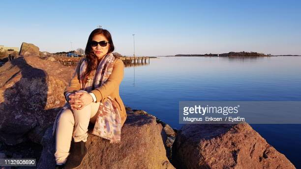 portrait of woman sitting on rock at beach against sky - eriksen stock pictures, royalty-free photos & images