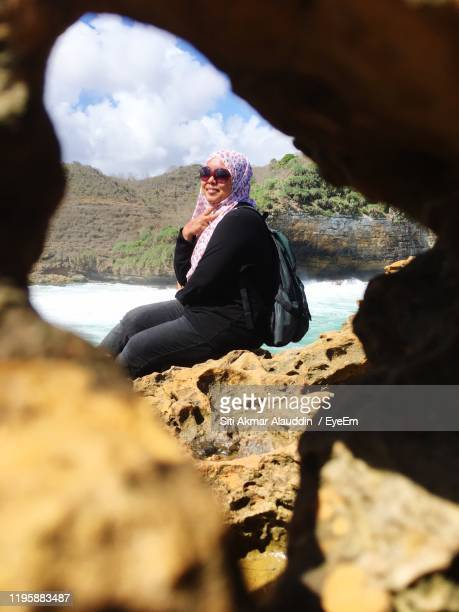 portrait of woman sitting on rock at beach seen through hole - cari stock pictures, royalty-free photos & images