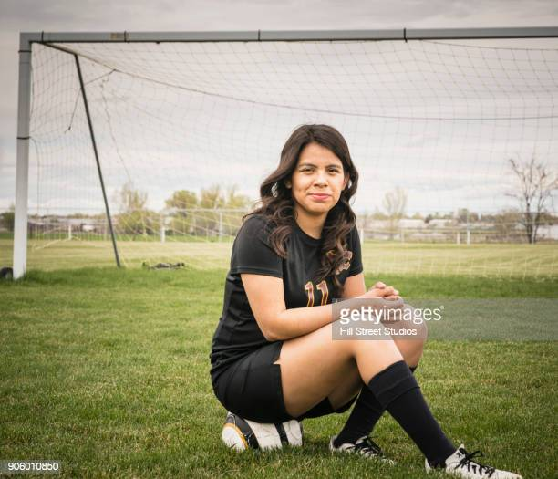 Portrait of woman sitting on soccer ball in field