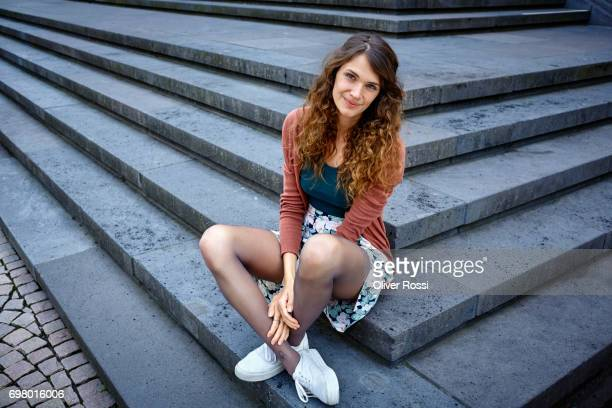 portrait of woman sitting on stairs outdoors - brown shoe stock pictures, royalty-free photos & images