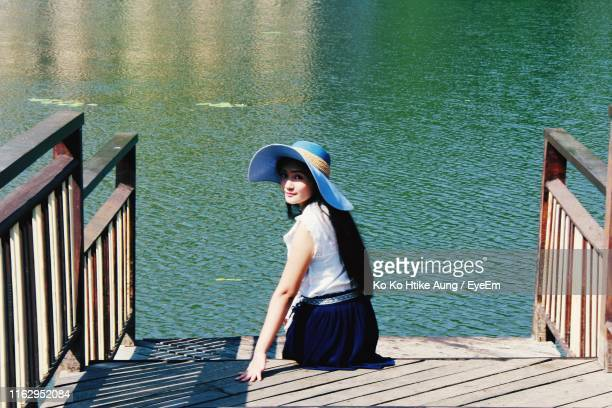 portrait of woman sitting on steps by lake - ko ko htike aung stock pictures, royalty-free photos & images