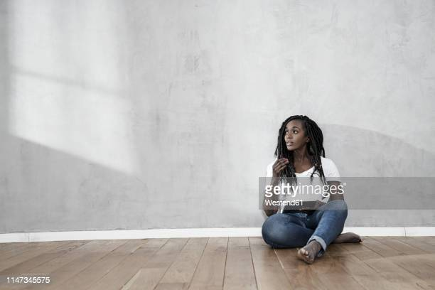 portrait of woman sitting on the floor with digital tablet - sitting on ground stock pictures, royalty-free photos & images
