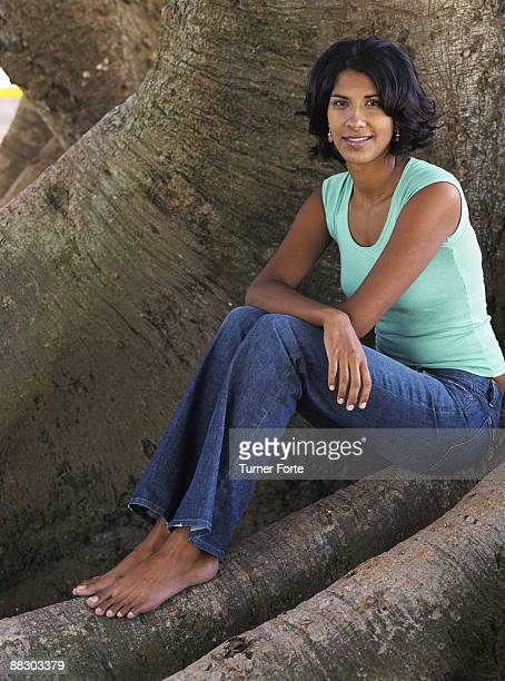 Portrait of woman sitting on tree roots