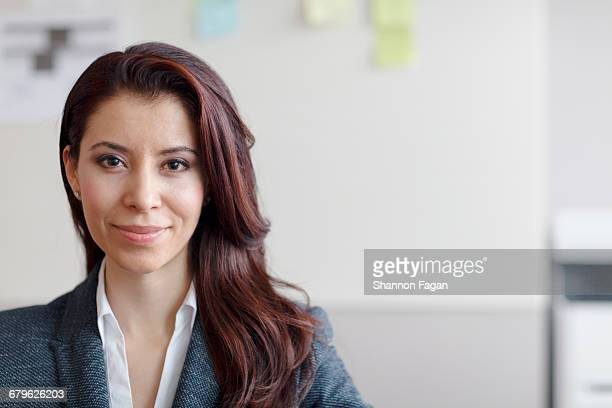 portrait of woman sitting smiling in office - 30 34 years stock pictures, royalty-free photos & images