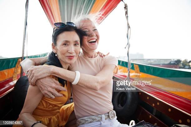 portrait of woman sitting with friend in boat - passagier wasserfahrzeug stock-fotos und bilder
