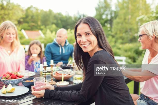 Portrait of woman sitting with friends and family at table in back yard during garden party