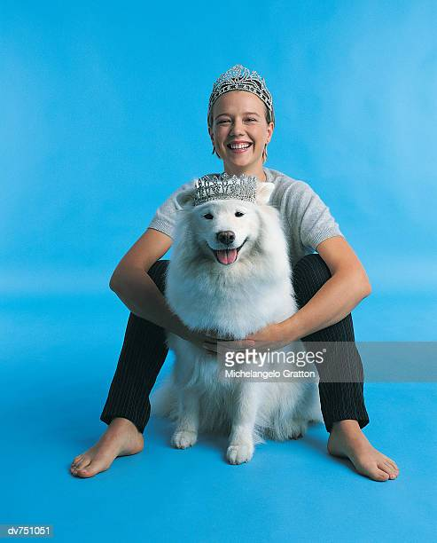 Portrait of Woman Sitting With Her Samoyed Wearing Tiaras