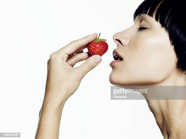 Portrait of woman smelling a strawberry