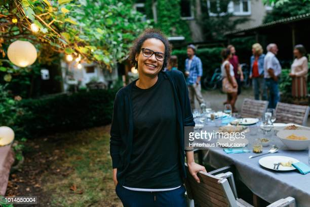 portrait of woman smiling at family bbq - incidental people stock pictures, royalty-free photos & images