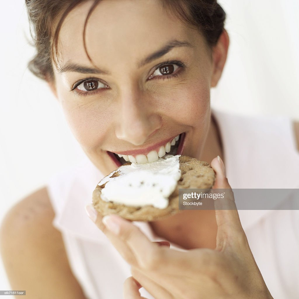 portrait of woman smiling biting a cracker with cheese : Stock Photo