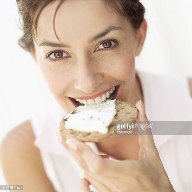 portrait of woman smiling biting a cracker with cheese
