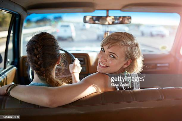 Portrait of woman smiling while friend driving