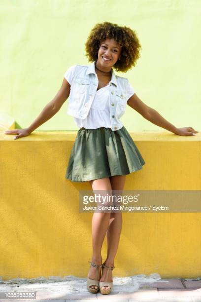 portrait of woman smiling while standing against yellow retaining wall - black skirt stock pictures, royalty-free photos & images
