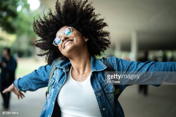 portrait of woman smiling with colorful background - alegria imagens e fotografias de stock