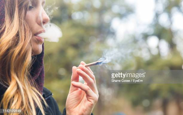 portrait of woman smoking marijuana joint outdoors - femme qui fume photos et images de collection